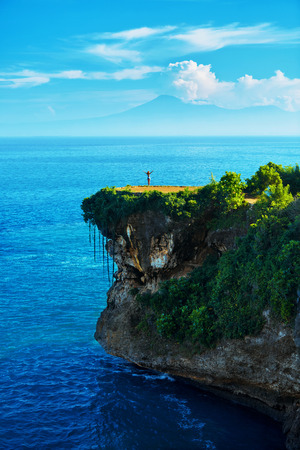 sea cliff: Nature Landscape. Scenic View Of Happy Free Woman With Hands Up On Beautiful Tropical Green Cliff, Sea Rock On Paradise Island. Blue Sky And Ocean On Background. Beauty Scenery. Summer Travel Vacation Stock Photo