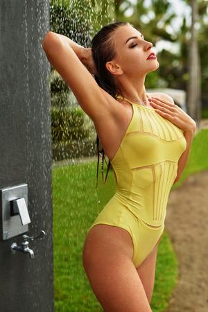 mujer bañandose: Mujer que toma la ducha de la piscina al aire libre. Primer de la muchacha hermosa apta Con Sexy Body En elegante de moda del traje de baño amarillo Ducharse bajo agua a Luxury Spa Resort Beach. Body Concept verano Cuidado de la Piel