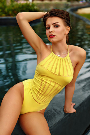sexy girl posing: Woman Summer Fashion. Healthy Happy Sexy Girl With Fit Body In Fashionable Swimsuit, Swimwear Sunbathing, Relaxing By Swimming Pool On Travel Holidays Vacation At Spa Hotel. Beauty, Wellness Lifestyle Stock Photo