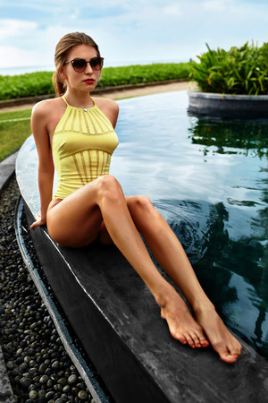 beauty body: Woman Summer Fashion. Healthy Happy Sexy Girl With Fit Body, Long Legs In Fashionable Swimsuit, Swimwear, Sunglasses Sunbathing By Swimming Pool On Travel Holidays Vacation. Beauty, Wellness Lifestyle Stock Photo