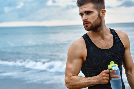 cuerpo hombre: Agua potable del hombre después de ejecutar entrenar en la playa. Retrato De Sediento Varón atlético sano con cuerpo en forma Beber Bebida refrescante, Descansar después de correr o Outdoor Training. Deportes, el concepto de fitness Foto de archivo