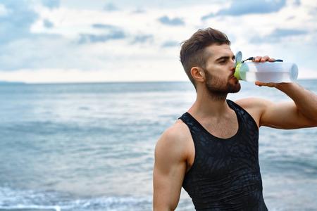 男のビーチでトレーニングを実行した後水を飲む。フィットのボディを実行中または屋外トレーニング後休んで、爽やかなドリンクを飲むとのどが