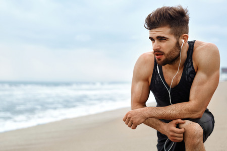 Portrait Of Athletic Man With Fit Muscular Body Resting After Jogging On Beach. Tired Exhausted Male Runner Taking A Break, Breathing After Running Workout Outdoor Near Ocean. Sports, Fitness Concept 版權商用圖片