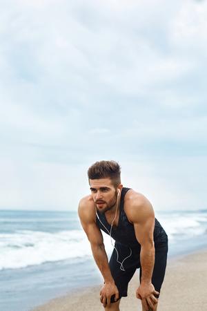 atmung: Portrait der athletischen Mann mit Fit Muskulös Körper Ruht Auf Strand Nach Joggen. Müde Erschöpft Male Runner Kaffee- oder Teepause, Atem Nach Lauftraining im Freien in der Nähe Ozean. Sport, Fitness Concept