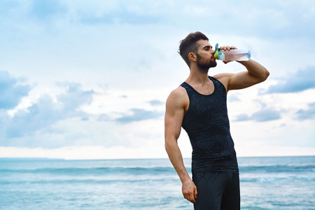 water sports: Man Drinking Water After Running Workout At Beach. Portrait Of Thirsty Healthy Athletic Male With Fit Body Drinking Refreshing Drink, Resting After Running Or Training Outdoor. Sports, Fitness Concept