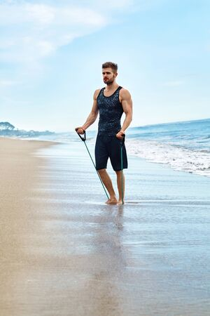outdoor sport: Exercise. Handsome Fit Athletic Man With Muscular Body Doing Stretching Expander Exercises On Sand. Sportsman Exercising At Beach. Sporty Male Training During Outdoor Workout. Sports, Fitness Concept