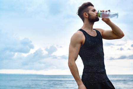 Man eau potable après l'exécution de la séance d'entraînement à la plage. Portrait Of Thirsty Healthy Homme Athletic Avec Fit Body Boire Boisson rafraîchissante, Se reposer après l'exécution ou la formation extérieure. Sports, Fitness Concept