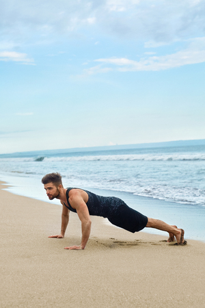 outdoor training: Sports. Sporty Handsome Male Doing Push Ups Exercise During Outdoor Workout At Beach. Fit Athletic Man With Muscular Body Exercising On Sand, Training Near Ocean. Fitness, Healthy Lifestyle Concept