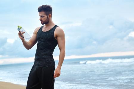 Retrato De Hombre Atlético saludable con cuerpo en forma con una botella de agua refrescante, reclina después de entrenamiento o correr en la playa. Hombre sed con una bebida después de entrenamiento al aire libre. Deportes, el concepto de fitness