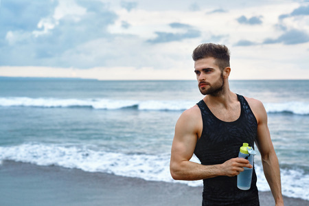 athletic body: Portrait Of Healthy Athletic Man With Fit Body Holding Bottle Of Refreshing Water, Resting After Workout Or Running At Beach. Thirsty Male With A Drink After Outdoor Training. Sports, Fitness Concept