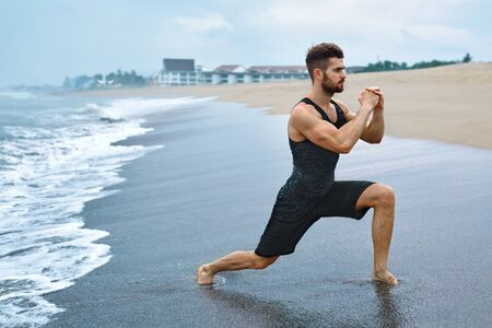 man legs: Fitness Exercise. Sporty Handsome Male Stretching Legs Before Run. Fit Athletic Man With Muscular Body Exercising On Sand, Training During Outdoor Workout At Beach. Sports, Healthy Lifestyle Concept
