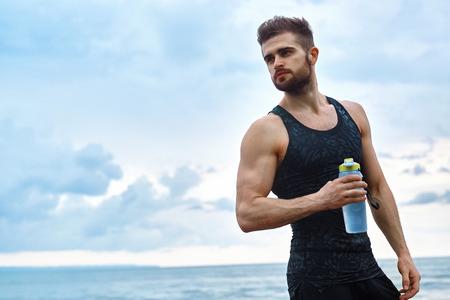 Portret van gezonde Atletische Mens Met Fit Body bedrijf fles verfrissende water, dat na training rust of hardlopen op het strand. Dorstig Man met een drankje na Outdoor Training. Sport, Fitness Concept