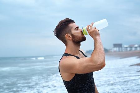 Man Trinkwasser nach dem Ausführen von Training am Strand. Porträt von Durst Gesundes Athletisch Mann Mit Fit Körpererfrischungsgetränk Trinken, Ruhen Nach Laufen oder Ausbildung im Freien. Sport, Fitness Concept