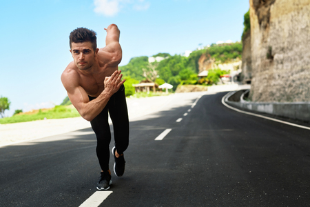 sports race: Athletics. Athletic Man With Fit Muscular Body In Starting Position For Running On Road. Handsome Runner Ready To Start Sprint Race. Fitness Model Training Outdoors In Summer. Sports Workout Concept