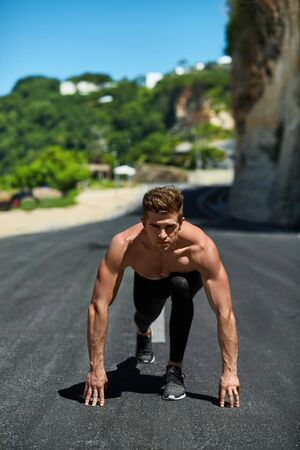 road position: Sports. Healthy Athletic Man With Fit Muscular Body In Starting Position For Running On Road. Handsome Runner Ready To Start Sprint Race. Fitness Model Training Outdoors In Summer. Workout Concept