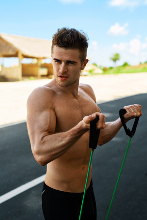 calisthenics: Sports Workout. Handsome Fitness Model Doing Expander Exercises And Training On Road In Summer. Athletic Man With Fit Muscular Body Exercising During Outdoor Workout. Healthy Active Lifestyle Concept