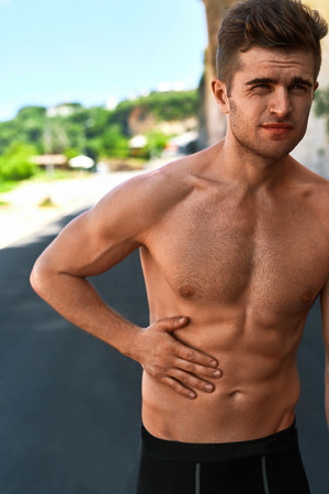 hurt: Stomach Ache. Closeup Portrait Of Athletic Man With Fit Muscular Body Touching Belly, Suffering From Abdominal Pain. Handsome Fitness Runner Feeling Bad After Running Outdoors. Sport Injury Concept