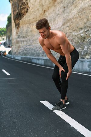 sportsmen: Sport Injury. Athletic Man With Fit Muscular Body Holding Painful Knee And Feeling Ache, Suffering From Pain. Handsome Fitness Runner Injured His Leg During Running Workout Training Outdoors.