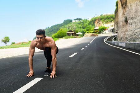 Sport. Gesunde Athletischer Mann mit Fit Muskulös Körper In Startposition für das Laufen auf der Straße. Gut aussehend Runner Bereit Sprint Rennen zu starten. Fitness Model Ausbildung im Sommer draußen. Trainingskonzept Standard-Bild