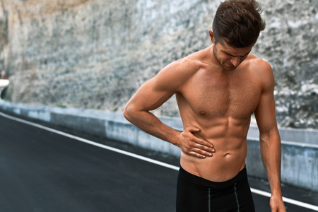 bad feeling: Stomach Ache. Closeup Portrait Of Athletic Man With Fit Muscular Body Touching Belly, Suffering From Abdominal Pain. Handsome Fitness Runner Feeling Bad After Running Outdoors. Sport Injury Concept