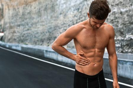 Dolor de estómago. Retrato de detalle de Hombre Atlético Con Muscular Body Fit Belly Tocar, que sufre de dolor abdominal. Apuesto gimnasio Runner sentirse mal después de ejecutar al aire libre. Concepto de lesiones de deporte