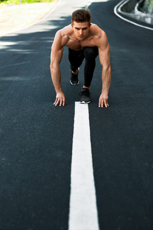 road position: Athletics. Athletic Man With Fit Muscular Body In Starting Position For Running On Road. Handsome Runner Ready To Start Sprint Race. Fitness Model Training Outdoors In Summer. Sports Workout Concept