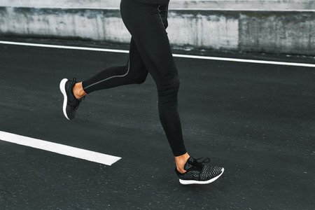 outdoor fitness: Sport. Close Up Of Sporty Male Legs In Sportwear And Sneakers Running On Road. Healthy Active Athletic Runner Man Jogging During Outdoor Workout, Exercising And Training For Marathon. Fitness Concept