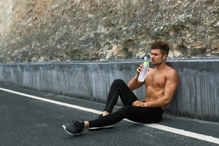 sediento: Tired Exhausted Athletic Man With Muscular Body Drinking Water, Resting After Running Workout. Thirsty Male Drinking Refreshing Drink After Outdoor Training On Hot Summer Day. Sports, Fitness Concept Foto de archivo