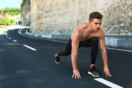 sports race: Sports. Healthy Athletic Man With Fit Muscular Body In Starting Position For Running On Road. Handsome Runner Ready To Start Sprint Race. Fitness Model Training Outdoors In Summer. Workout Concept