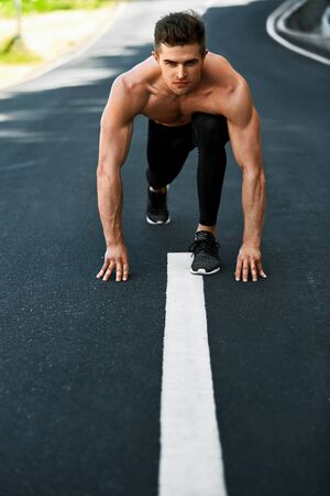 sports training: Athletics. Athletic Man With Fit Muscular Body In Starting Position For Running On Road. Handsome Runner Ready To Start Sprint Race. Fitness Model Training Outdoors In Summer. Sports Workout Concept