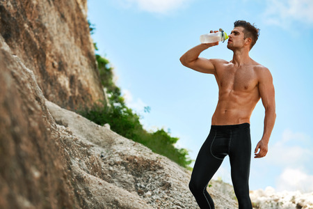 Tired Exhausted Athletic Man With Muscular Body Drinking Water, Resting After Running Workout. Thirsty Male Drinking Refreshing Drink After Outdoor Training On Hot Summer Day. Sports, Fitness Concept