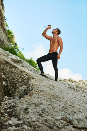 male body: Tired Exhausted Athletic Man With Muscular Body Drinking Water, Resting After Running Workout. Thirsty Male Drinking Refreshing Drink After Outdoor Training On Hot Summer Day. Sports, Fitness Concept Stock Photo