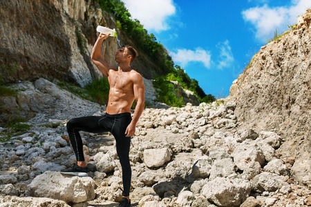 male body: Tired Athletic Man With Muscular Body Pouring Water Over Face, Resting After Running Workout. Thirsty Male Refreshing After Exercising Outdoors On Hot Summer Day. Sports, Fitness Concept