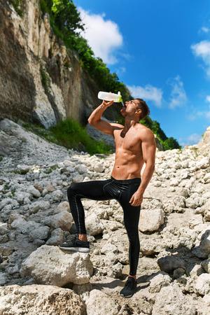 sediento: Cansado Agotada Hombre Atlético con cuerpo musculoso Agua potable, Descansando después de ejecutar entrenamiento. Hombre sediento que bebe la bebida refrescante Después del entrenamiento al aire libre en día de verano caliente. Deportes, el concepto de fitness