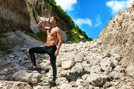 agotado: Cansado Agotada Hombre Atlético con cuerpo musculoso Agua potable, Descansando después de ejecutar entrenamiento. Hombre sediento que bebe la bebida refrescante Después del entrenamiento al aire libre en día de verano caliente. Deportes, el concepto de fitness