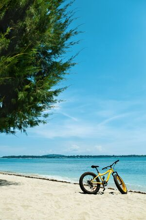 sporting equipment: Summer Sports. Yellow Sand Bicycle Standing On Tropical Sea Beach. Ride Bike On Holidays Travel Vacation. Sport Equipment, Healthy Active Lifestyle, Recreational Leisure Sporting Activity Concepts Stock Photo