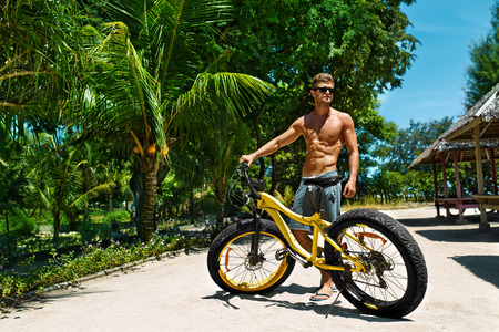 resort beach: Summer Fun. Handsome Athletic Sexy Man In Sunglasses With Sport Bicycle Sunbathing On Tropical Beach Resort. Fitness Male With Bike Tanning, Relaxing On Travel Vacation. Healthy Lifestyle, Recreation Stock Photo