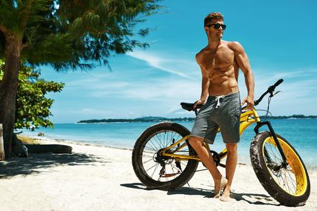 Knappe gespierde man met geel zand Fiets Ontspannen On Shore Op Zomer Reizen strandvakantie. Fitness Male Model Met Fiets zonnen bij Oceaan. Sporten en recreatie in Summertime Concept