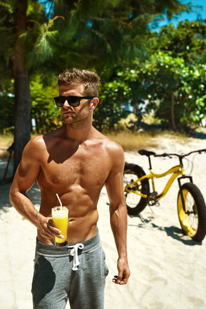 body torso: Summer Vacations. Man With Fit Sexy Body And Muscular Torso Drinking Fresh Juice Smoothie Cocktail On Tropical Beach After Riding Bicycle. Handsome Fitness Male Model Enjoying Refreshing Healthy Drink