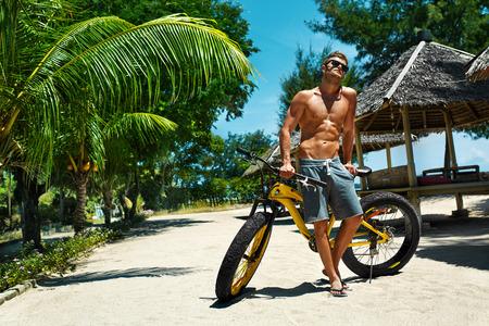 여름 재미. 열 대 해변 리조트에서 스포츠 자전거 일광욕 잘 생긴 운동 섹시한 남자 선글라스. 휘트니스 남자와 자전거 태닝, 여행 휴가에 휴식. 건강한