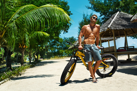 Summer Fun. Handsome Athletic Sexy Man In Sunglasses With Sport Bicycle Sunbathing On Tropical Beach Resort. Fitness Male With Bike Tanning, Relaxing On Travel Vacation. Healthy Lifestyle, Recreation Imagens