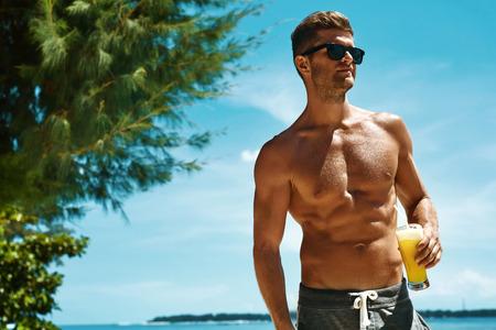 atletismo: Bebida saludable. Tener guapo modelo masculino ejercicio en diversión, disfrutando de las vacaciones del viaje. Retrato del hombre atractivo atlético con el cuerpo muscular que bebe Refrescante cóctel de jugo tropical en la playa de mar. Verano