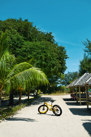 sporting activity: Summer Sports. Yellow Sand Bicycle Standing On Tropical Sea Beach Resort. Ride Bike On Holidays Travel Vacation. Sport Equipment, Healthy Active Lifestyle, Recreational Sporting Activity Concepts Stock Photo