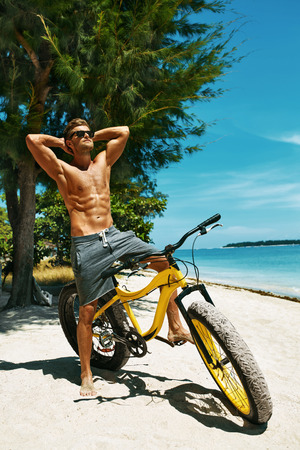 male body: Fitness Male Model With Bike Sunbathing On Sun, Enjoying Summer Travel Vacation. Handsome Sexy Man In Sunglasses With Muscular Body, Healthy Tan Skin Tanning Near Bicycle On Sand Beach. Summertime Stock Photo