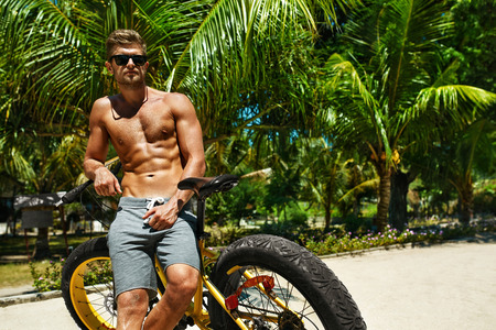 fit: Summer Fun. Handsome Athletic Sexy Man In Sunglasses With Sport Bicycle Sunbathing On Tropical Beach Resort. Fitness Male With Bike Tanning, Relaxing On Travel Vacation. Healthy Lifestyle, Recreation Stock Photo
