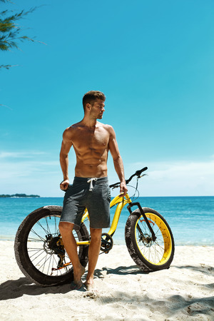 fit: Handsome Muscular Man With Yellow Sand Bicycle Relaxing On Shore On Summer Travel Beach Vacation. Fitness Male Model With Bike Sunbathing By Ocean. Sports Activity And Recreation In Summertime Concept