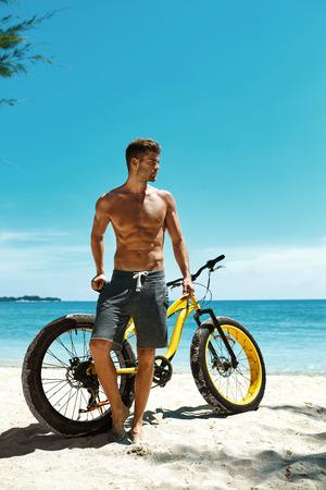 Hombre muscular hermoso con el amarillo de la arena de bicicletas que se relaja en la orilla en la playa del verano viaje de vacaciones. Modelo de la aptitud Hombre Con La Bici tomando el sol en Océano. Deportivos y recreativos en verano Concepto
