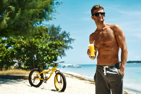 tomando jugo: Summer Vacations. Man With Fit Sexy Body And Muscular Torso Drinking Fresh Juice Smoothie Cocktail On Tropical Beach After Riding Bicycle. Handsome Fitness Male Model Enjoying Refreshing Healthy Drink
