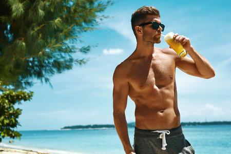 Gesundes Getränk. Gut aussehend Fitness Male Model, die Spaß haben, genießen Reisen Urlaub. Porträt von Athletic sexy Mann mit dem muskulösen Körper erfrischenden Saft Cocktail auf tropischen Meer Strand Trinken. Sommer