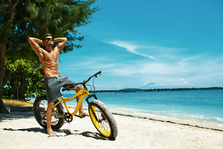 sunny beach: Fitness Male Model With Bike Sunbathing On Sun, Enjoying Summer Travel Vacation. Handsome Sexy Man In Sunglasses With Muscular Body, Healthy Tan Skin Tanning Near Bicycle On Sand Beach. Summertime Stock Photo